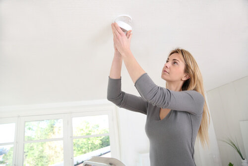 woman installing smoke detector home safety