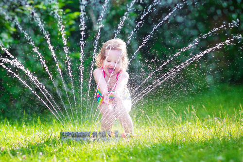little girl sprinkler backyard