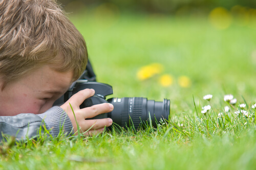 kid with camera taking pictures lawn
