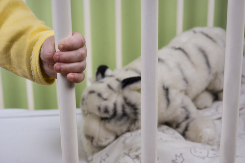 baby in crib hand holding crib bars