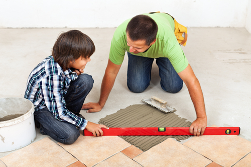father and son laying tile flooring