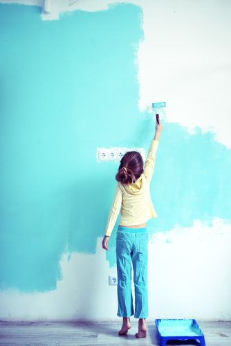 little girl painting a blue wall